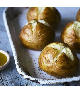 Four ready baked jacket potatoes drizzled with extra virgin olive oil